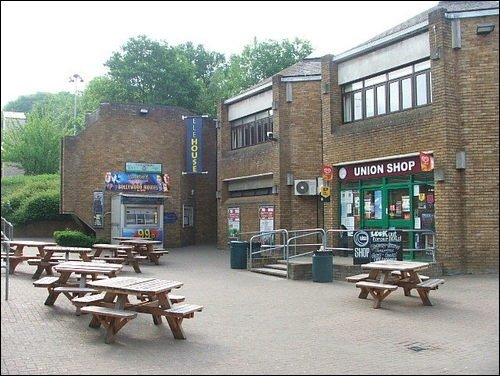 Hertfordshire - a square with a shop and tables and benches